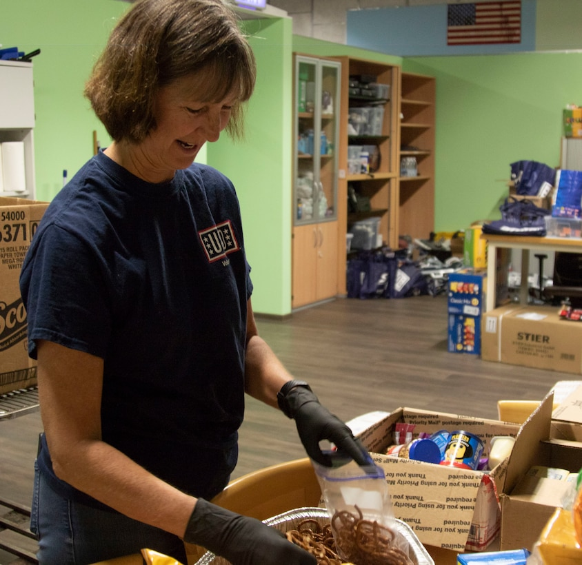 Jean Wash, a USO volunteer and Army spouse fills bags with snacks for Soldiers at the Deployment Processing Center, Rhine Ordnance Barracks in Kaiserslautern, Germany September 15, 2020. The DPC currently houses incoming personnel from the United States undergoing quarantine and in-processing to the European theater. The USO's mission is to strengthen America's military service members by keeping them connected to family, home and country, throughout their service to the nation. (U.S. Army Reserve photo by Staff Sgt. Chris Jackson/Released)