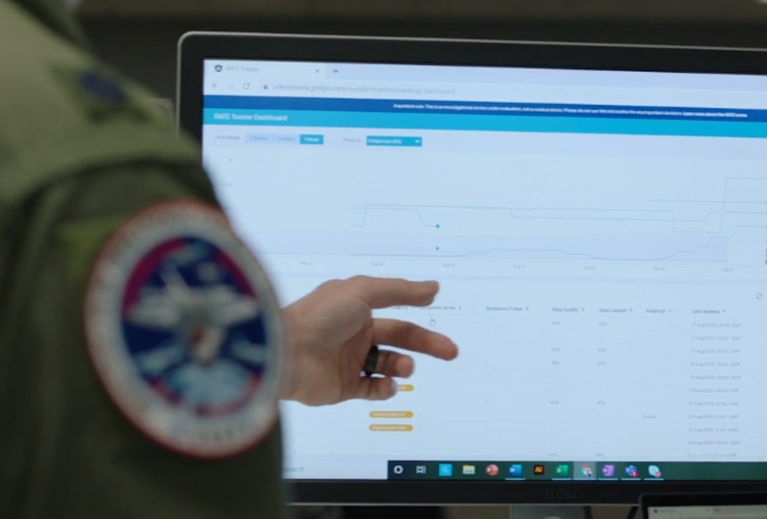 An airman points at a computer screen.