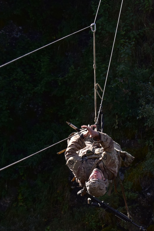 Basic Military Mountaineering Course student Spc. Kevin Vang crosses a rope bridge over a mountain gorge at the Northern Warfare Training Center's Black Rapids Site during training. NWTC cadre followed Coronavirus restrictions while guiding students through both the basic and advanced mountaineering courses in August. With the advent of Alaska's long, cold winter, NWTC's focus is now shifting to cold weather training for the 2020-21 season.