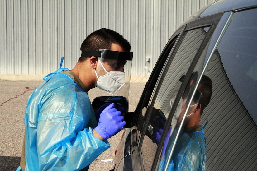 A man wearing personal protective equipment looks through the window of a car.