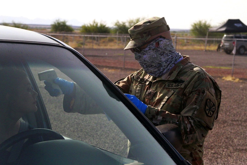 A soldier wearing a face covering aims a thermometer at a driver's forehead.