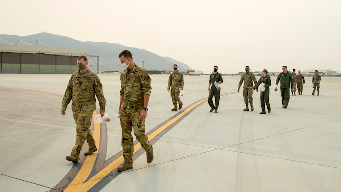Airmen perform a foreign-object damage walk during Exercise Agile Reaper, Sept. 11, 2020, at Naval Air Station Point Mugu, California. FOD walks are conducted to ensure flight lines are free of debris in order to execute mission sorties as safe as possible. (U.S. Air Force photo by Senior Airman Collette Brooks)
