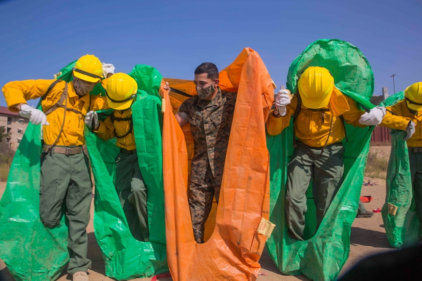 A Marine helps service members put on protective coverings.