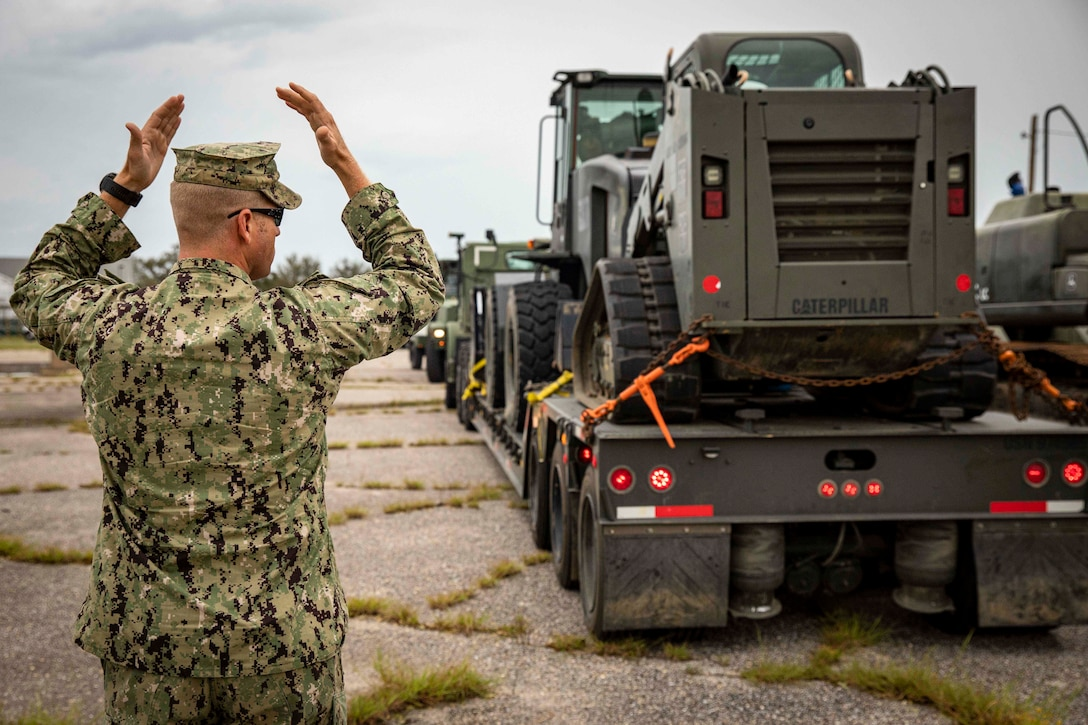 A sailor signals other sailors in military vehicles.