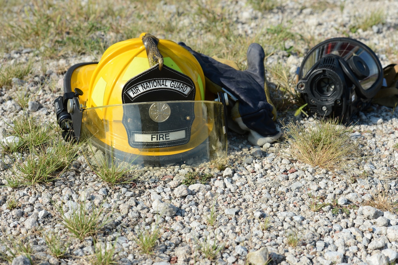 A yellow firefighter helmet sits on the ground next to other gear.