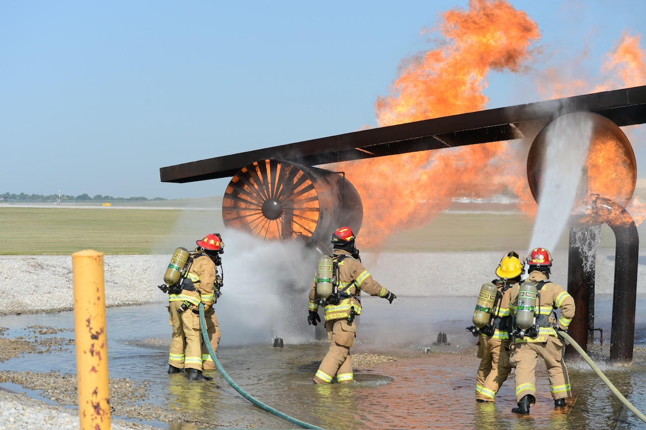 Firefighters spray water onto a fire.