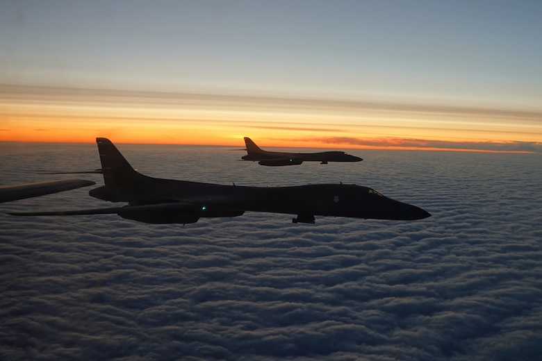 Photo of two B-1's flying over clouds