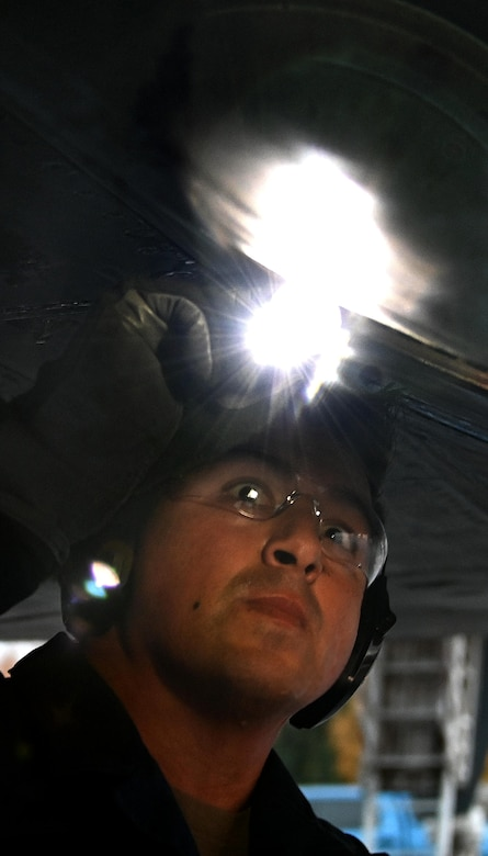 Photo of Airman inspecting B-1 with a flashlight