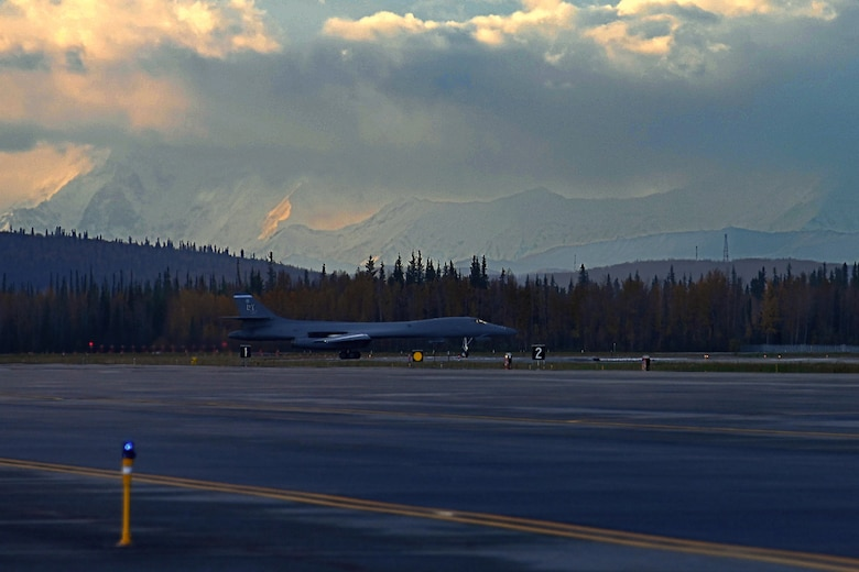Photo of B-1 with snow-capped mountains in background