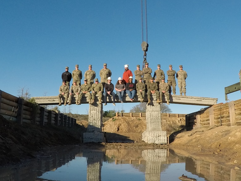 The U.S. Army Engineer Research and Development Center, Construction Engineer Research Laboratory's Additive Construction team poses with Marines from the 7th Engineer Support Battalion, Naval Mobile Construction Battalion 5, atop a 3D printed bridge, Camp Pendleton, Calif. The teams collaborated to test the constructability of the bridge in December 2018.
