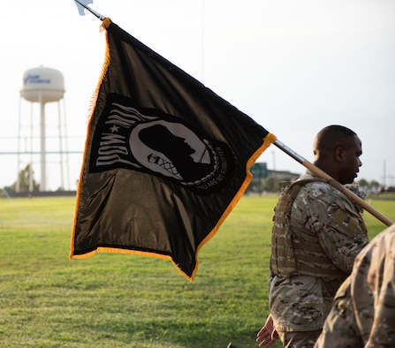 Chief Master Sgt. Robert L. Zackery III, 47th FTW command chief master sergeant, carries the prisoner of war and missing in action flag while walking around the track on Sept. 17, 2020 at Laughlin Air Force Base, Texas. The flag is a symbol of our Nation's concern and commitment to resolving, as fully as possible, the fates of Americans still prisoner, missing and unaccounted.