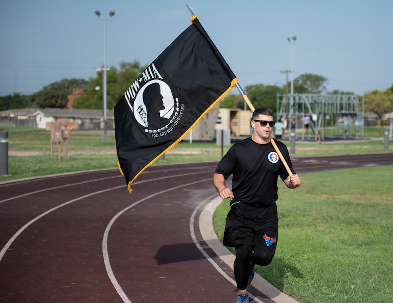 Tech. Sgt. Christopher Johnson, Honor Guard NCO in charge, runs around the track while carrying the prisoner of war and missing in action flag on Sept. 17, 2020 at Laughlin Air Force Base, Texas. Johnson ran the track while proudly carrying the flag to show his respect and raise awareness of POW/MIA military members.