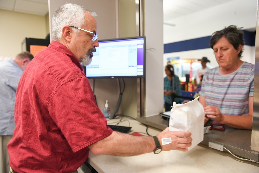 Pharmacy technician Andy Pollaehne hands a prescription to Cary Fisher at the Satellite Pharmacy located inside the AAFES Base Exchange at Hill Air Force Base. Beginning Nov. 2, the Satellite Pharmacy windows will reopen.
