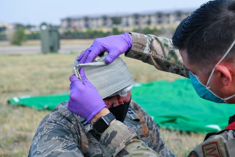 An Airman from the 460th Medical Group applies a bandage to a victim with a head wound during the Ready Eagle exercise where a simulated explosion occurred Sept. 18, 2020, at the Air Reserve Personnel Center on Buckley Air Force Base, Colo.
