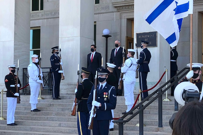 Two men stand at the top of steps amid a color guard.