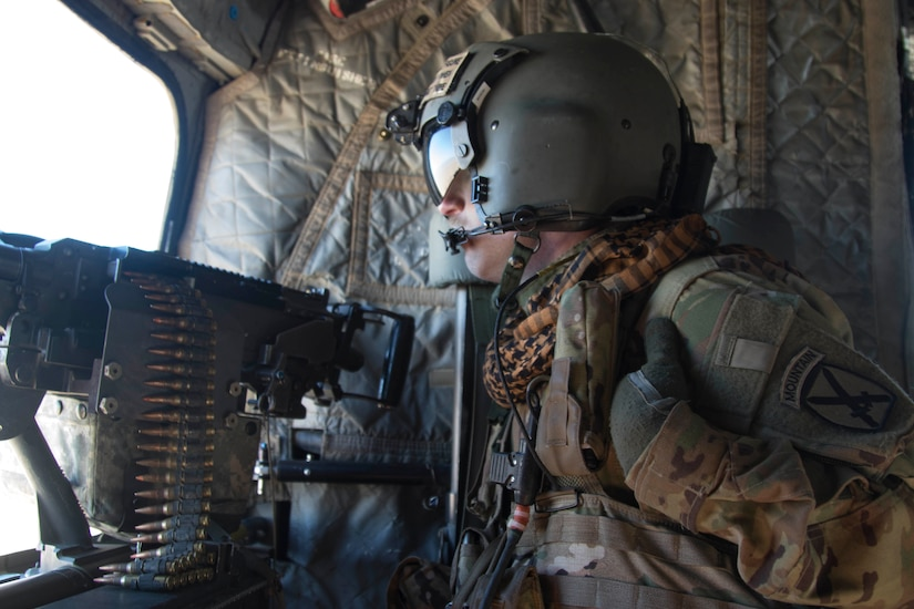 A soldier looks out the window of a helicopter. He sits near a machine gun.