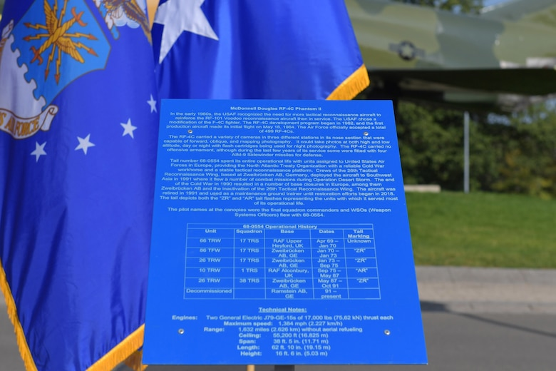 A historical information plate stands in front of an aircraft static display.