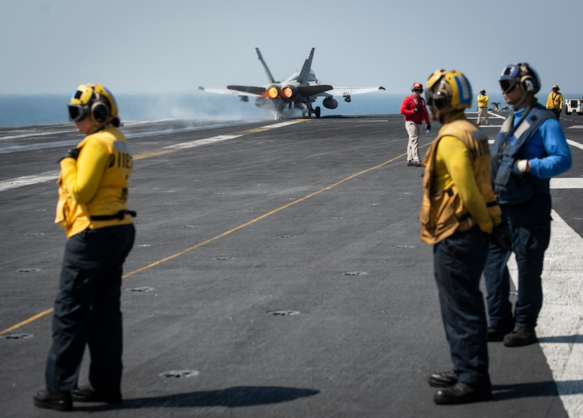 An F/A-18C Hornet launches from the flight deck of an aircraft carrier.