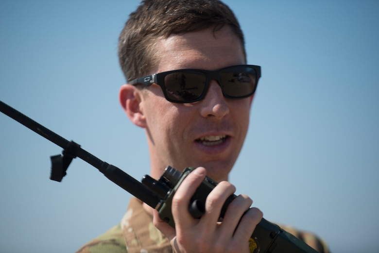 An Airman relays information on a radio.