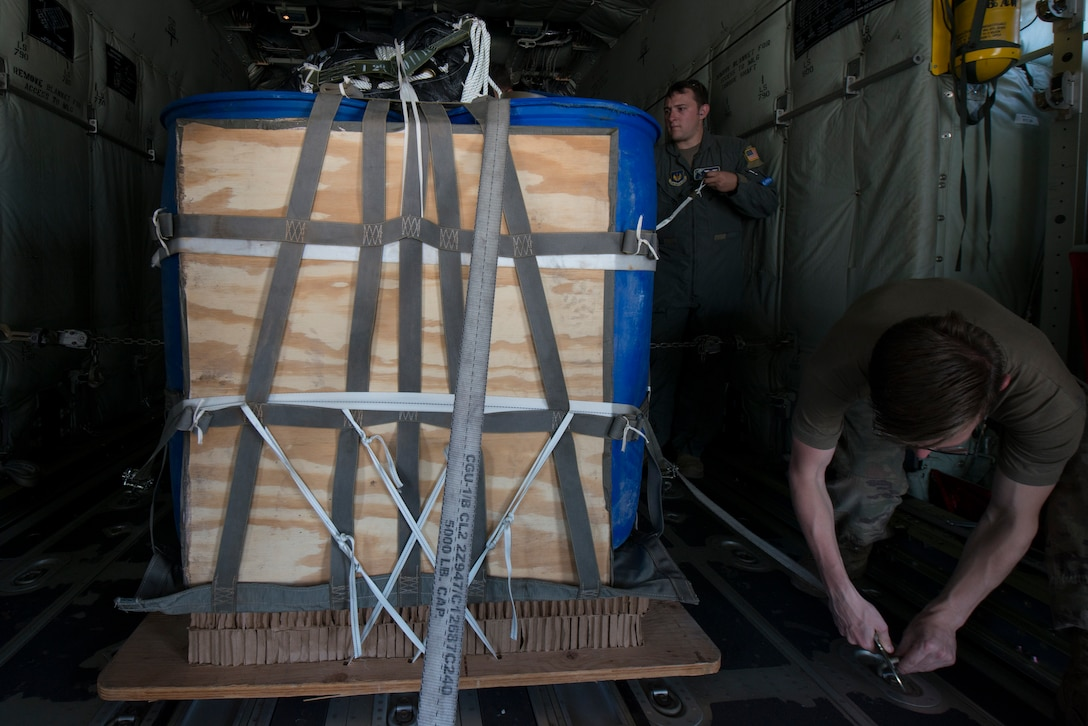 Airmen secure a high velocity container delivery system to a C-130J aircraft.