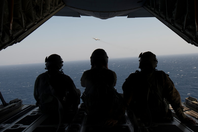 Airmen watch a plane fly over while on a plane.
