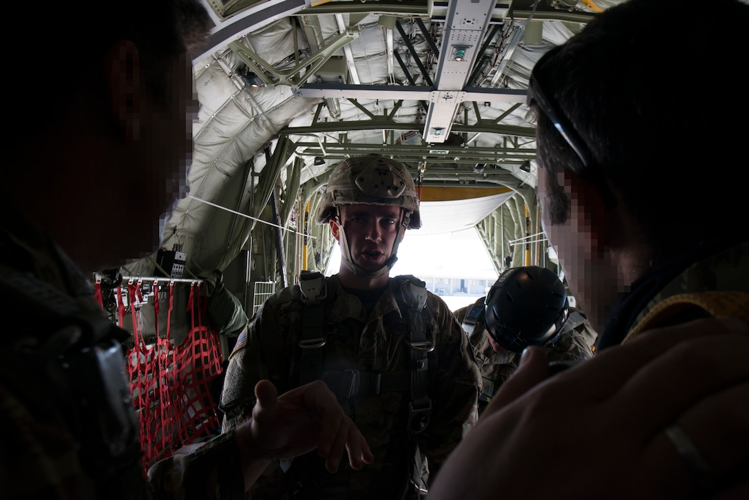 An Army paratrooper speaks with Hellenic forces members.