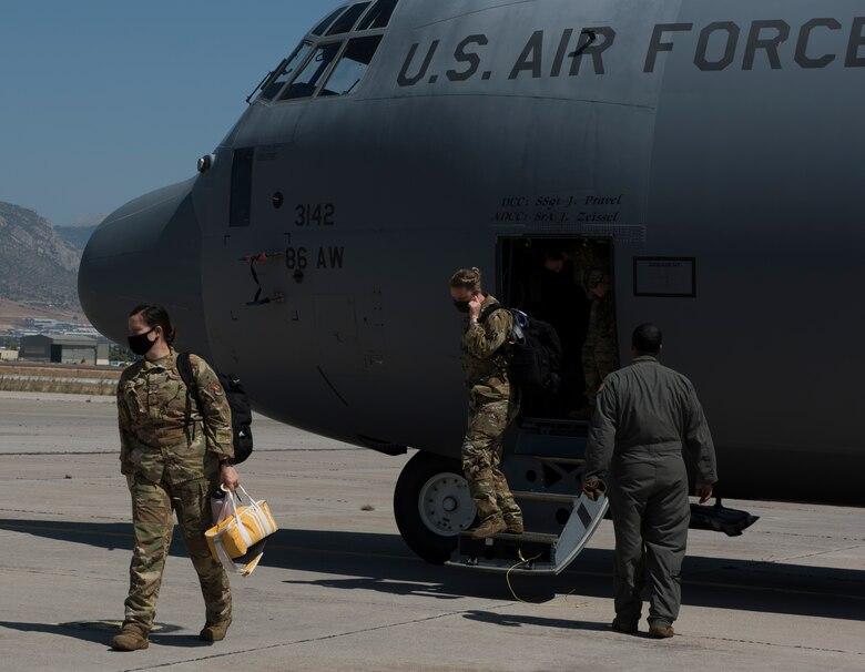 Airmen depart a C-130J aircraft.