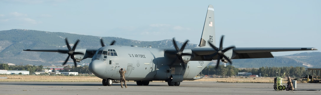 An Airman assigned to the 86th Maintenance Squadron marshals a C-130J aircraft.