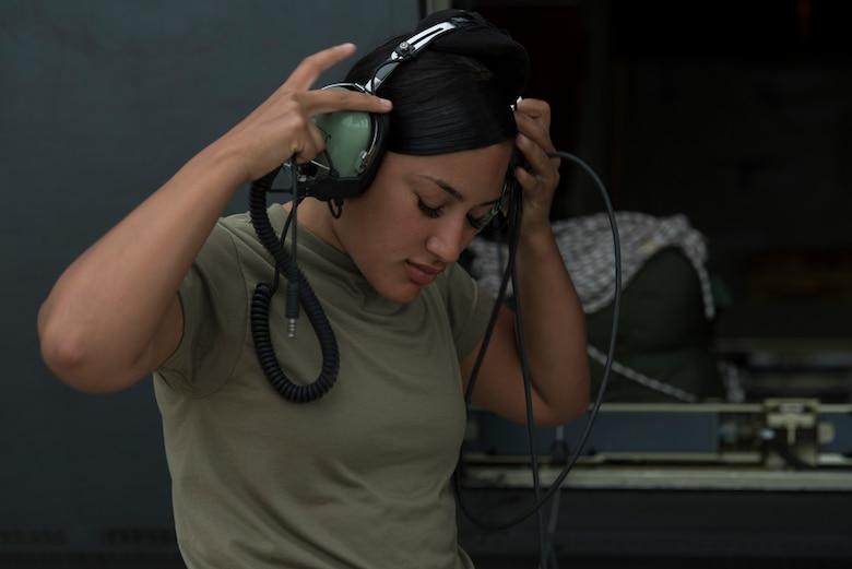 An Airman puts on earphones.