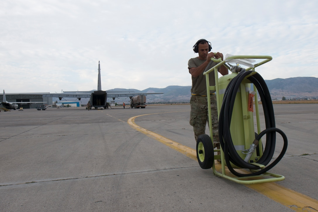 An Airman places a fire extinguisher in front of a C-130J aircraft.