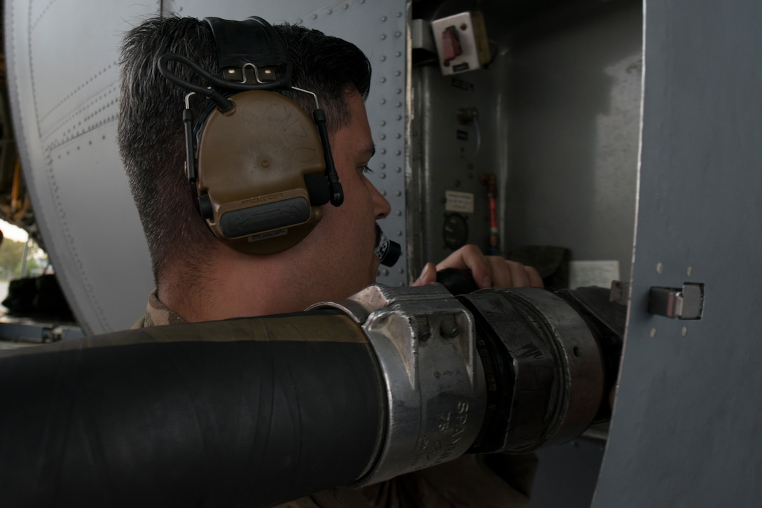 An Airman gives fuel to a C-130J aircraft.