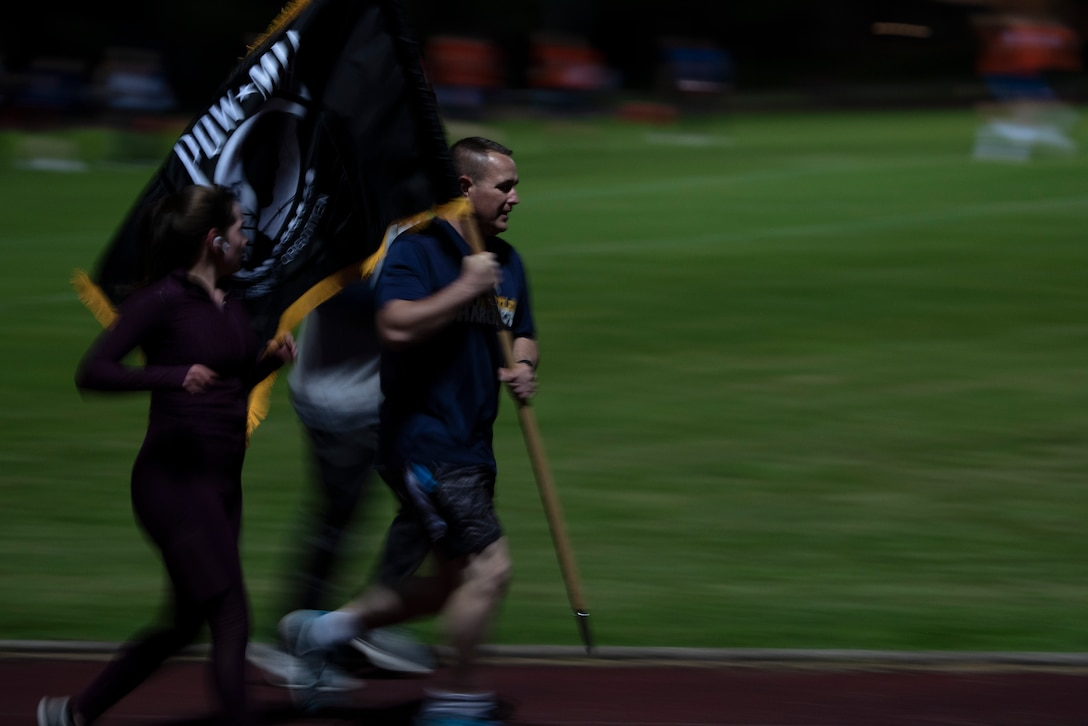 U.S. Air Force Master Sgt. Matthew Plew and Senior Airman Mikayla Whiteley, run with the POW/MIA flag at Royal Air Force Lakenheath, England, Sept. 17, 2020. Members of the 48th Fighter Wing kept the flag in constant motion for 24 hours in honor of more than 82,000 Americans who were Prisoners of War and Missing in Action from past conflicts. (U.S. Air Force photo by Airman 1st Class Jessi Monte)