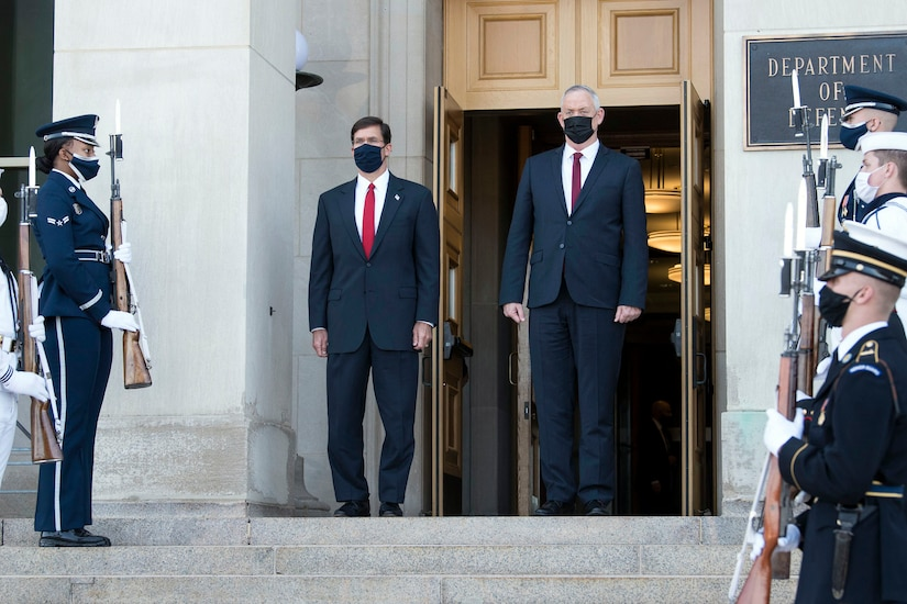 Two men wearing facemasks stand at the top of the Pentagon steps.