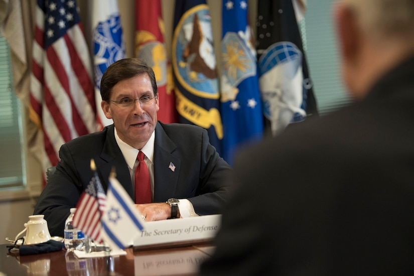 Defense Secretary Dr. Mark T. Esper speaks to another man sitting across from him at a table.