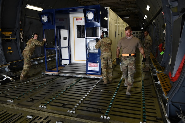 Airmen prepare to off load a specialized medical container designed to transport individuals with infectious diseases at Al Udeid Air Base, Qatar, Sept. 18, 2020. The Negatively Pressurized Conex, or NPC, is configured for the C-17 Globemaster III and C-5 Super Galaxy aircraft to safely transport up to 28 passengers or 23 patients, including ambulatory and litter, around the globe. (U.S. Air Force photo by Staff Sgt. Kayla White)