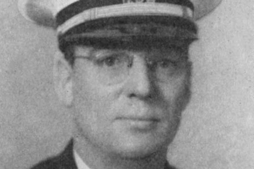 A man in a suit and Navy cap looks forward.