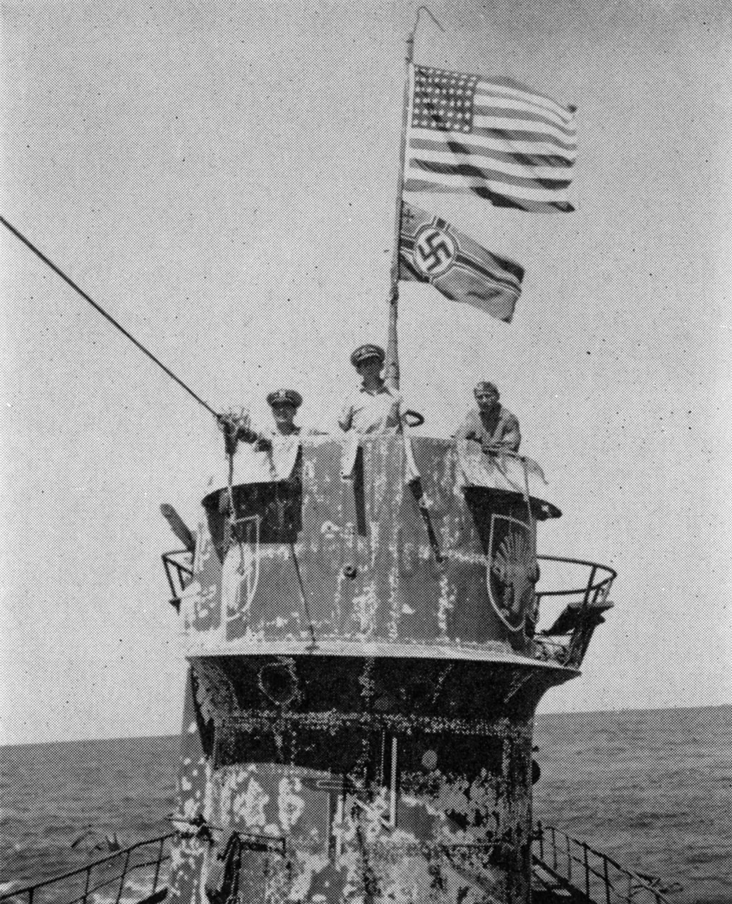 Two flags fly above three men standing on the conning tower of a submarine in the ocean.