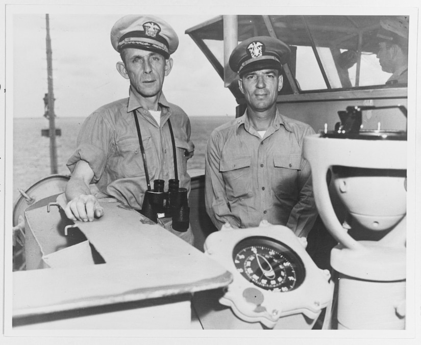 Two sailors pose for a photograph near the bridge of a ship.