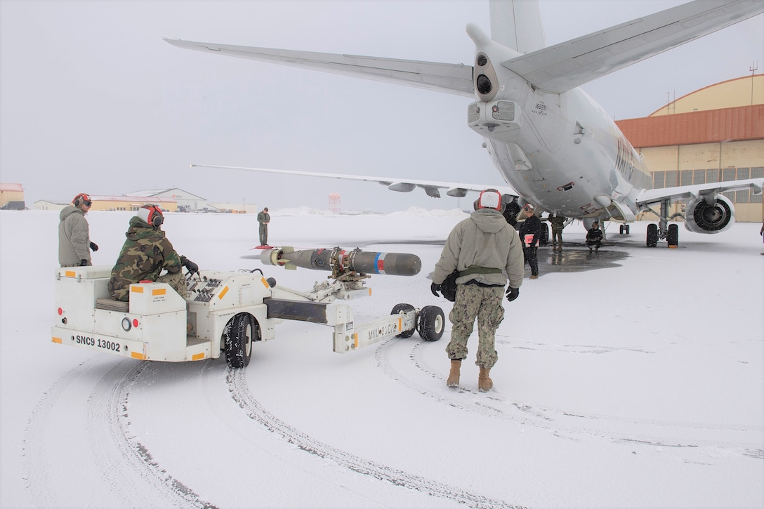Personnel use a munitions handling unit to transport a torpedo to a P-8A Poseidon at Naval Air Station Keflavik.