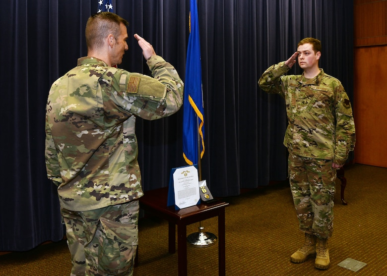 Col. Patrick Williams, 557th Weather Wing commander, presents the Air Force Commendation Medal to Tech. Sgt. Alex Brosnahan, 2d Weather Squadron, for saving another service member's life on Aug. 4, 2020 at Offutt Air Force Base, Nebraska.