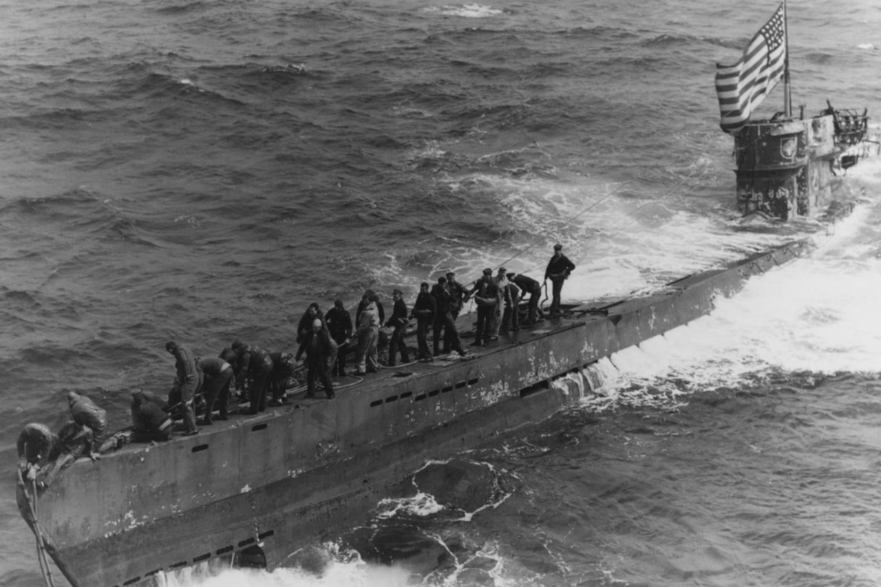 Several men stand on the topside of a partially submerged submarine that's flying a U.S. flag.