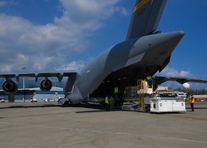 Military personnel offload a mobile field hospital from a C-17 Globemaster III at Norman Manley International Airport in Kingston, Jamaica, Sept. 19, 2020.