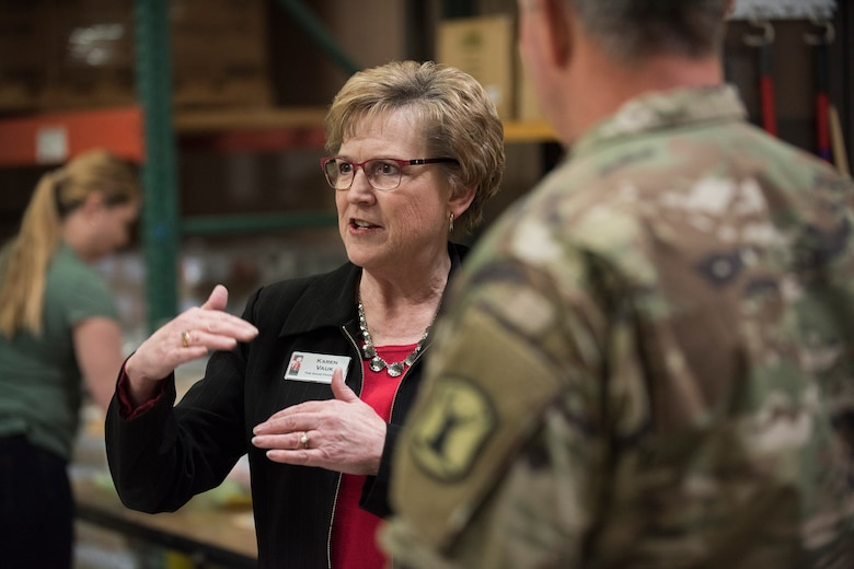 Karen Vauk the director of the Idaho Foodbank, a white female with dirty blonde hair and glasses, wearing a red shirt and black blazer jacket, gestures with her hands as she talks with Airmen and Soldiers from the Idaho National Guard inside a food pantry.