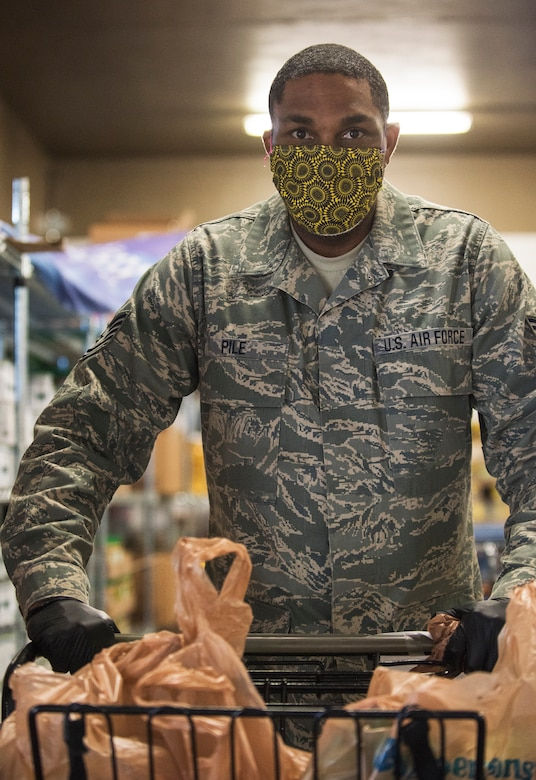 An Airman wearing a yellow paisley mask and gloves, pushes a shopping cart loaded with various groceries inside a food pantry.