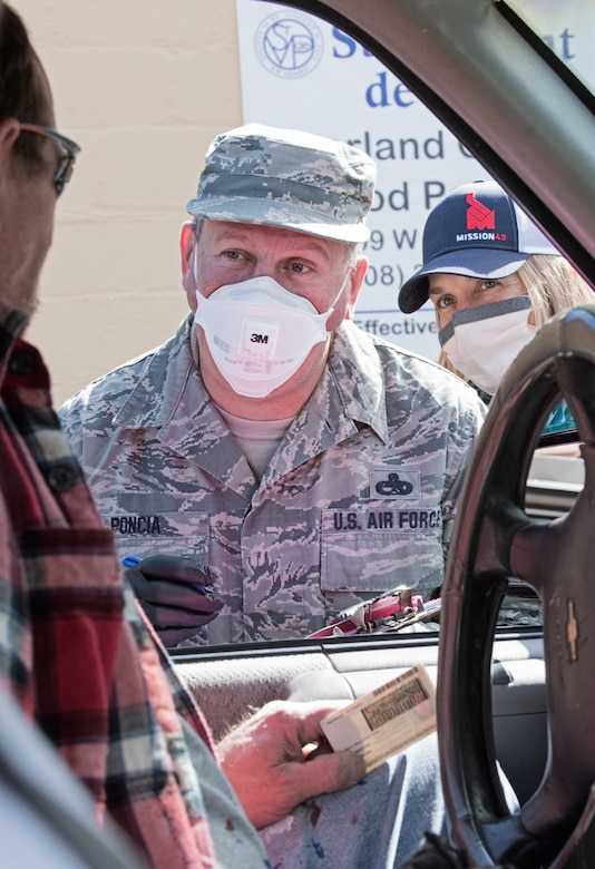 An Airman wearing a white mask and black gloves, listen and prepares to write down information onto a clip board from a man wearing glasses and red and black flannel shirt inside his chevy vehicle.