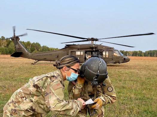 An Aerospace Medical Technician with the 148th Fighter Wing, Minnesota Air National Guard, communicates with a Critical Care Flight Paramedic assigned to the 2-211 General Aviation Support Battalion, Minnesota Army National Guard, during medical evacuation training at Camp Ripley Training Center, Minnesota on Saturday, September 20, 2020.