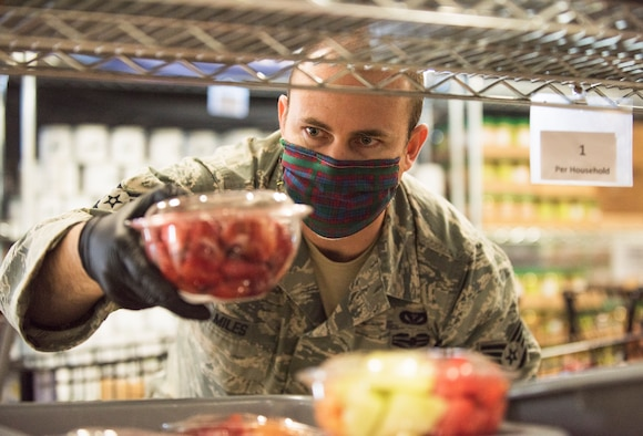 An Airman wearing a mask and gloves, places a plastic container with red strawberries onto a shelf with other fruits.