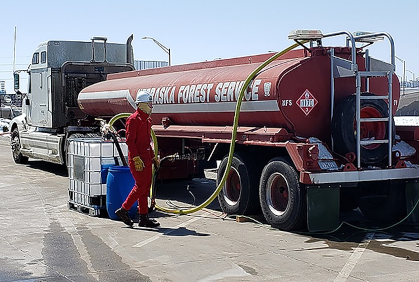 A man in safety equipment unloads a red tanker truck into a cubical container attached to a pallet.