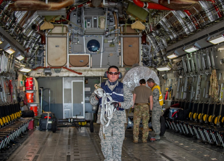 An Airman wearing an Air Force uniform, a blue vest, sunglasses, and ear muff hearing protection, bundles up a cargo strap as he walks away from an A-10 Thunderbolt II engine that was just loaded onto the back of a C-17 Globemaster II. Two Airmen inspect the cargo in the background, one of the Airmen is wearing a yellow reflective vest.