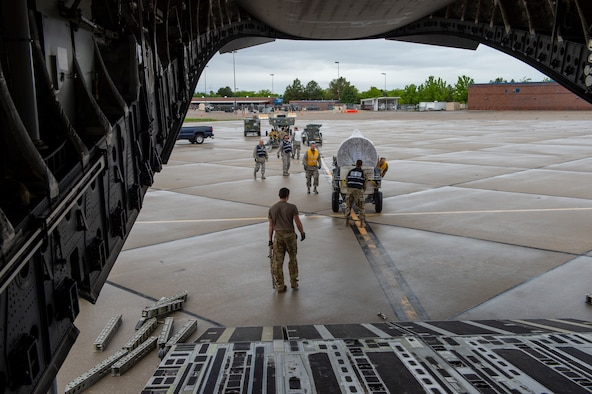 Airmen push cargo onto the back of an Air Force C-17 Globemaster III. The cargo is lined up on a wet flightline ramp with several pieces of cargo waiting to be loaded by a handful of Airmen.